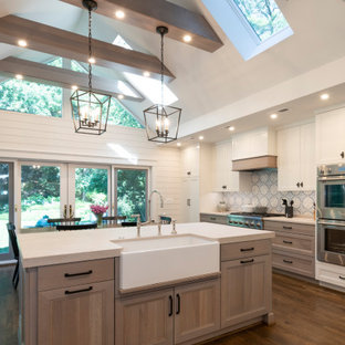 Large transitional kitchen designs - Inspiration for a large transitional l-shaped medium tone wood floor, brown floor and exposed beam kitchen remodel in DC Metro with a farmhouse sink, light wood cabinets, multicolored backsplash, stainless steel appliances, white countertops and recessed-panel cabinets