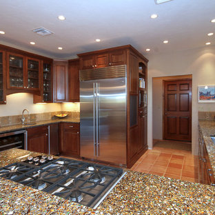 Photo of a large transitional u-shaped eat-in kitchen in Phoenix with a single-bowl sink, raised-panel cabinets, brown cabinets, recycled glass benchtops, beige splashback, stone tile splashback, stainless steel appliances and terra-cotta floors.