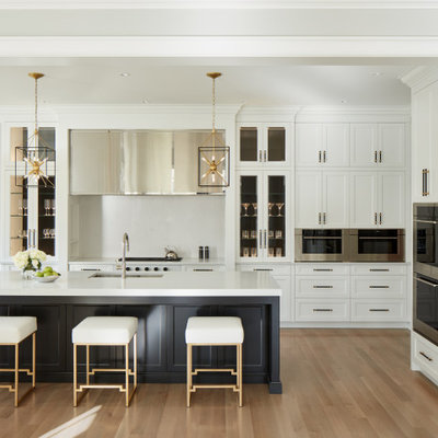 Example of a mid-sized transitional l-shaped light wood floor and gray floor eat-in kitchen design in Chicago with an undermount sink, white cabinets, quartz countertops, white backsplash, stone slab backsplash, stainless steel appliances, an island, white countertops and shaker cabinets