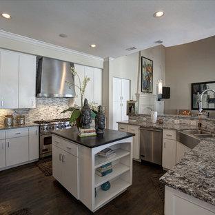 ダラスの大きい地中海スタイルのおしゃれなキッチン (エプロンフロントシンク、フラットパネル扉のキャビネット、白いキャビネット、マルチカラーのキッチンパネル、ボーダータイルのキッチンパネル、シルバーの調理設備の、濃色無垢フローリング) の写真