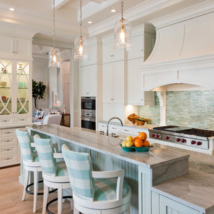 Transitional kitchen inspiration - Inspiration for a transitional l-shaped light wood floor kitchen remodel in Miami with shaker cabinets, white cabinets, green backsplash, matchstick tile backsplash, stainless steel appliances and an island