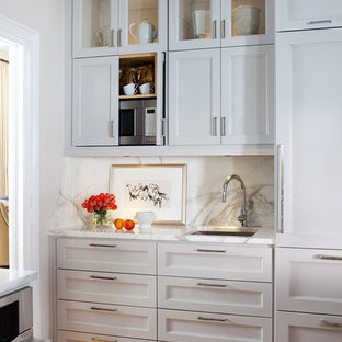 Transitional eat-in kitchen ideas - Inspiration for a transitional l-shaped eat-in kitchen remodel in Atlanta with an undermount sink, recessed-panel cabinets, gray cabinets, marble countertops, white backsplash, paneled appliances and marble backsplash