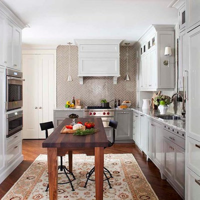 Inspiration for a transitional l-shaped enclosed kitchen remodel in Atlanta with an undermount sink, recessed-panel cabinets, gray cabinets, granite countertops, beige backsplash, subway tile backsplash and paneled appliances