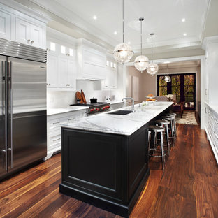 Inspiration for a transitional galley eat-in kitchen remodel in Toronto with an undermount sink, recessed-panel cabinets, white cabinets, marble countertops, white backsplash and stainless steel appliances
