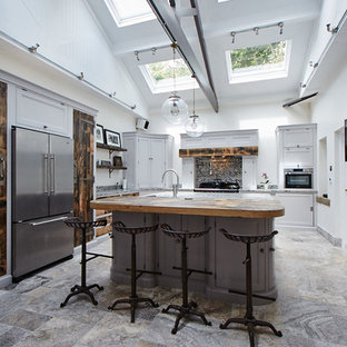 This is an example of a large classic l-shaped kitchen in Other with grey cabinets, stainless steel appliances, an island, recessed-panel cabinets, multi-coloured splashback, stone slab splashback and multi-coloured floors.