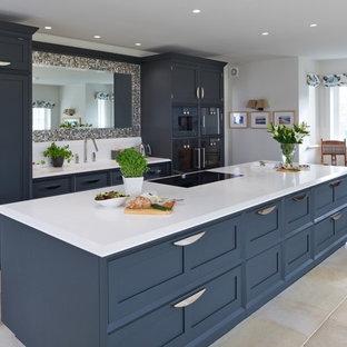 他の地域の中くらいのトランジショナルスタイルのおしゃれなキッチン (シェーカースタイル扉のキャビネット、青いキャビネット、ミラータイルのキッチンパネル、黒い調理設備、ベージュの床、ベージュのキッチンカウンター、アンダーカウンターシンク) の写真