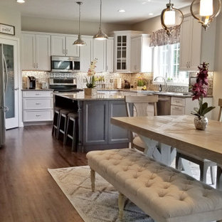 Mid-sized transitional u-shaped eat-in kitchen in Other with a farmhouse sink, recessed-panel cabinets, white cabinets, granite benchtops, metallic splashback, metal splashback, stainless steel appliances, vinyl floors, with island, multi-coloured floor and grey benchtop.