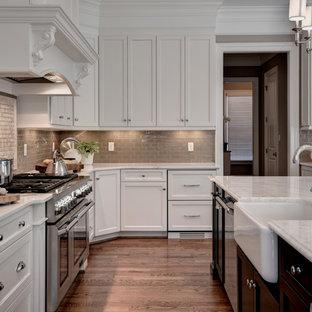 Geräumige Klassische Wohnküche in L-Form mit Landhausspüle, Schrankfronten im Shaker-Stil, weißen Schränken, Marmor-Arbeitsplatte, Küchenrückwand in Beige, Rückwand aus Glasfliesen, Küchengeräten aus Edelstahl, braunem Holzboden, Kücheninsel und braunem Boden in Sonstige