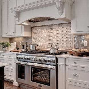 Huge elegant l-shaped medium tone wood floor and brown floor eat-in kitchen photo in Other with a farmhouse sink, shaker cabinets, white cabinets, marble countertops, beige backsplash, glass tile backsplash, stainless steel appliances and an island