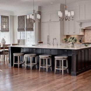 他の地域の巨大なトランジショナルスタイルのおしゃれなキッチン (エプロンフロントシンク、シェーカースタイル扉のキャビネット、白いキャビネット、大理石カウンター、ベージュキッチンパネル、ガラスタイルのキッチンパネル、シルバーの調理設備、無垢フローリング、茶色い床) の写真