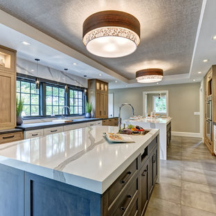 Large transitional galley eat-in kitchen in New York with an undermount sink, shaker cabinets, grey cabinets, quartz benchtops, white splashback, stone slab splashback, stainless steel appliances, porcelain floors, multiple islands, brown floor and white benchtop.