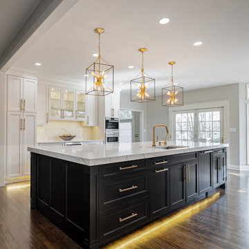 Transitional kitchen with dark and light cabinets and gold accents