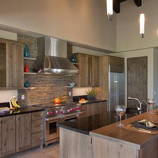 Imagen de cocina de galera, tradicional renovada, con electrodomésticos de acero inoxidable, encimera de granito, armarios estilo shaker, puertas de armario de madera oscura y salpicadero de pizarra
