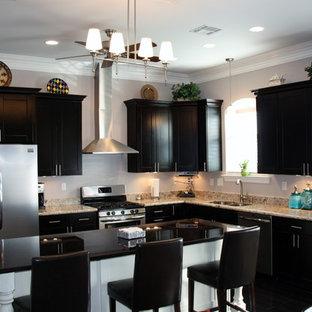 Ispirazione per una cucina classica di medie dimensioni con lavello sottopiano, ante in stile shaker, ante nere, top in granito, paraspruzzi beige, paraspruzzi in lastra di pietra, elettrodomestici in acciaio inossidabile, parquet scuro, isola e pavimento nero