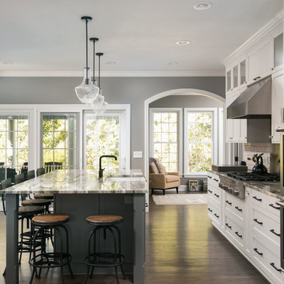 Large elegant dark wood floor and brown floor kitchen photo in Cleveland with a farmhouse sink, recessed-panel cabinets, white cabinets, stainless steel appliances, an island, subway tile backsplash, quartzite countertops and white backsplash