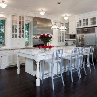Klassische Küche in L-Form mit Edelstahl-Arbeitsplatte, Glasfronten, weißen Schränken und Küchengeräten aus Edelstahl in Toronto