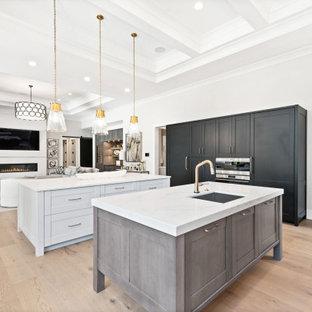 Idées déco pour une très grand cuisine classique en U avec un évier encastré, un placard à porte shaker, des portes de placard grises, un plan de travail en quartz modifié, une crédence blanche, une crédence en quartz modifié, un électroménager en acier inoxydable, un sol en bois clair, 2 îlots, un sol marron, un plan de travail blanc et un plafond à caissons.