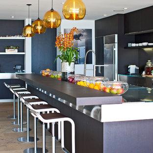 Große Moderne Wohnküche in L-Form mit Einbauwaschbecken, flächenbündigen Schrankfronten, dunklen Holzschränken, Edelstahl-Arbeitsplatte, Küchengeräten aus Edelstahl, Travertin, Kücheninsel und beigem Boden in Los Angeles