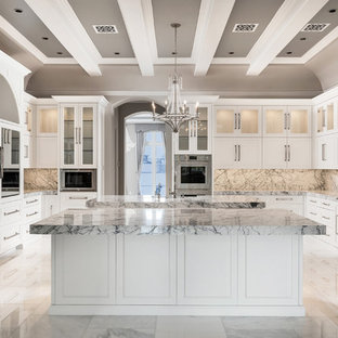 This is an example of an expansive transitional u-shaped separate kitchen in Phoenix with a farmhouse sink, raised-panel cabinets, white cabinets, marble benchtops, multi-coloured splashback, marble splashback, stainless steel appliances, marble floors, multiple islands, multi-coloured floor and multi-coloured benchtop.