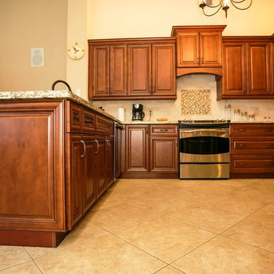 Mid-sized transitional u-shaped porcelain tile eat-in kitchen photo in Miami with an undermount sink, raised-panel cabinets, brown cabinets, granite countertops, beige backsplash, stone tile backsplash, stainless steel appliances and a peninsula