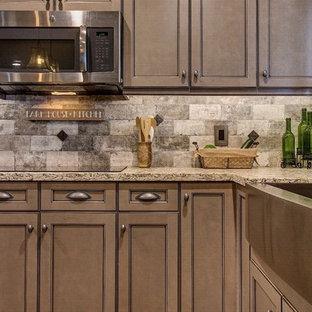 Geräumige Klassische Wohnküche in U-Form mit Landhausspüle, Schrankfronten mit vertiefter Füllung, braunen Schränken, Granit-Arbeitsplatte, Küchenrückwand in Grau, Rückwand aus Steinfliesen, Küchengeräten aus Edelstahl, braunem Holzboden und Kücheninsel in Phoenix