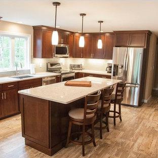ボストンの中くらいのトランジショナルスタイルのおしゃれなキッチン (アンダーカウンターシンク、落し込みパネル扉のキャビネット、茶色いキャビネット、クオーツストーンカウンター、青いキッチンパネル、ガラスタイルのキッチンパネル、シルバーの調理設備、クッションフロア、茶色い床、ベージュのキッチンカウンター) の写真