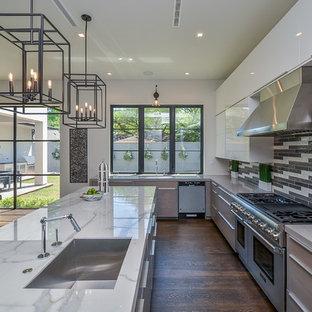 Offene, Mittelgroße Klassische Küche in L-Form mit Waschbecken, flächenbündigen Schrankfronten, weißen Schränken, Marmor-Arbeitsplatte, bunter Rückwand, Rückwand aus Glasfliesen, Küchengeräten aus Edelstahl, braunem Holzboden, Kücheninsel und weißer Arbeitsplatte in Houston
