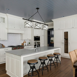Example of a classic medium tone wood floor eat-in kitchen design in Minneapolis with a farmhouse sink, raised-panel cabinets, white cabinets, white backsplash, subway tile backsplash, paneled appliances, an island and gray countertops
