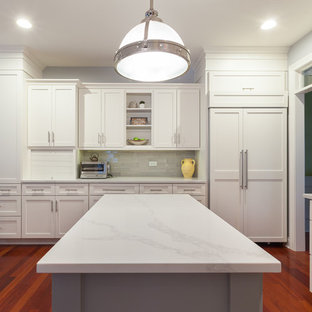 Large transitional u-shaped eat-in kitchen in Chicago with an undermount sink, shaker cabinets, white cabinets, quartz benchtops, grey splashback, glass tile splashback, stainless steel appliances, medium hardwood floors, with island and red floor.