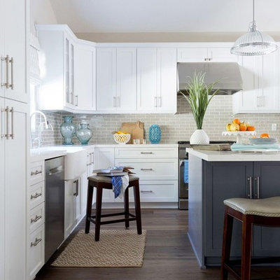 Inspiration for a huge transitional l-shaped medium tone wood floor open concept kitchen remodel in Los Angeles with a farmhouse sink, shaker cabinets, white cabinets, quartz countertops, gray backsplash, subway tile backsplash, stainless steel appliances and an island
