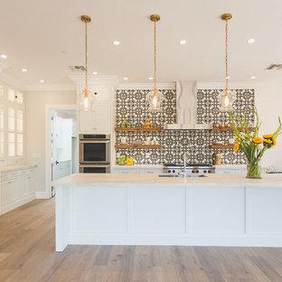 Zweizeilige, Große Klassische Wohnküche mit weißen Schränken, Küchengeräten aus Edelstahl, Kücheninsel, Doppelwaschbecken, Schrankfronten mit vertiefter Füllung, bunter Rückwand, braunem Holzboden, Quarzwerkstein-Arbeitsplatte, Rückwand aus Zementfliesen, braunem Boden und weißer Arbeitsplatte in Phoenix