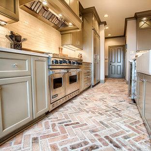 バーミングハムの広いトランジショナルスタイルのおしゃれなキッチン (エプロンフロントシンク、フラットパネル扉のキャビネット、グレーのキャビネット、珪岩カウンター、グレーのキッチンパネル、サブウェイタイルのキッチンパネル、シルバーの調理設備、レンガの床、マルチカラーの床) の写真