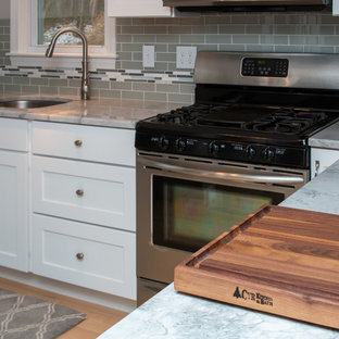 Mid-sized transitional eat-in kitchen ideas - Inspiration for a mid-sized transitional u-shaped light wood floor and brown floor eat-in kitchen remodel in Boston with a single-bowl sink, flat-panel cabinets, white cabinets, granite countertops, gray backsplash, subway tile backsplash, stainless steel appliances, a peninsula and white countertops