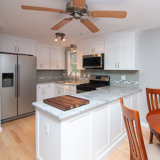 Mid-sized transitional eat-in kitchen inspiration - Example of a mid-sized transitional u-shaped light wood floor and brown floor eat-in kitchen design in Boston with a single-bowl sink, flat-panel cabinets, white cabinets, granite countertops, gray backsplash, subway tile backsplash, stainless steel appliances, a peninsula and white countertops