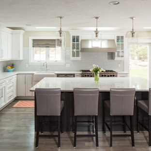 Inspiration for a large classic l-shaped kitchen/diner in Boston with a belfast sink, recessed-panel cabinets, white cabinets, stainless steel appliances, an island, engineered stone countertops, green splashback, glass tiled splashback, porcelain flooring and brown floors.