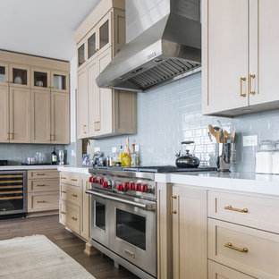 Inspiration for a large transitional u-shaped kitchen in Chicago with an undermount sink, shaker cabinets, beige cabinets, quartz benchtops, glass tile splashback, stainless steel appliances, medium hardwood floors, with island, brown floor and white benchtop.