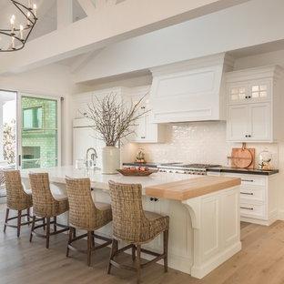 Maritime Küche mit Schrankfronten im Shaker-Stil, weißen Schränken, Küchenrückwand in Weiß, Küchengeräten aus Edelstahl, hellem Holzboden, Kücheninsel, beigem Boden und schwarzer Arbeitsplatte in San Diego