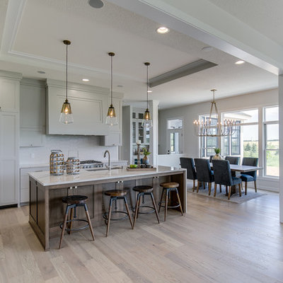 Inspiration for a large transitional l-shaped light wood floor and beige floor eat-in kitchen remodel in Minneapolis with an undermount sink, shaker cabinets, white cabinets, quartzite countertops, white backsplash, ceramic backsplash, paneled appliances, an island and white countertops