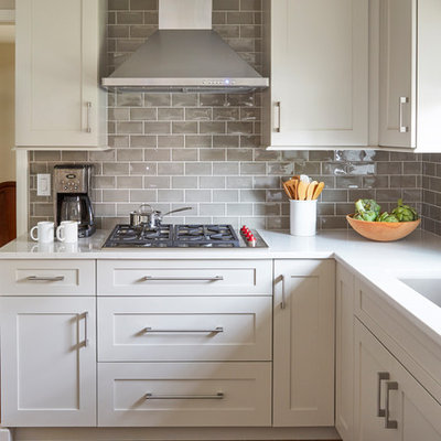 Example of a mid-sized transitional u-shaped medium tone wood floor and brown floor eat-in kitchen design in Chicago with an undermount sink, shaker cabinets, white cabinets, quartz countertops, gray backsplash, subway tile backsplash, paneled appliances, a peninsula and white countertops