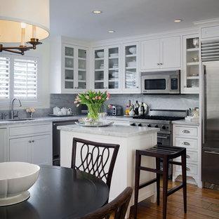Klassisk inredning av ett litet kök, med rostfria vitvaror, luckor med glaspanel, vita skåp, en undermonterad diskho, stänkskydd i sten, marmorbänkskiva, en köksö, grått stänkskydd och mellanmörkt trägolv