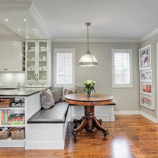 Idee per una cucina abitabile chic con lavello sottopiano, ante con riquadro incassato, elettrodomestici bianchi e pavimento in legno massello medio
