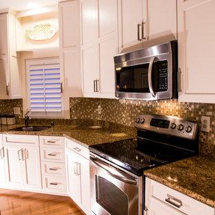 Mittelgroße Klassische Küche in L-Form mit Unterbauwaschbecken, Schrankfronten mit vertiefter Füllung, weißen Schränken, Granit-Arbeitsplatte, Küchenrückwand in Braun, Rückwand aus Mosaikfliesen, Küchengeräten aus Edelstahl, braunem Holzboden und Kücheninsel in Baltimore