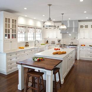 Mittelgroße Klassische Küche in U-Form mit Landhausspüle, Kassettenfronten, weißen Schränken, Marmor-Arbeitsplatte, Küchenrückwand in Weiß, Rückwand aus Metrofliesen, Küchengeräten aus Edelstahl, dunklem Holzboden, Kücheninsel und weißer Arbeitsplatte in New York