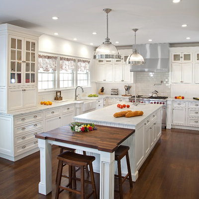 Kitchen - mid-sized traditional dark wood floor kitchen idea in New York with a farmhouse sink, beaded inset cabinets, white cabinets, marble countertops, white backsplash, subway tile backsplash, stainless steel appliances, an island and white countertops
