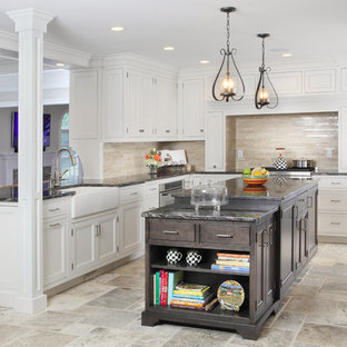 Design ideas for a large traditional l-shaped kitchen/diner in New York with beaded cabinets, a belfast sink, granite worktops, travertine flooring, white cabinets, beige splashback, an island, stainless steel appliances and travertine splashback.