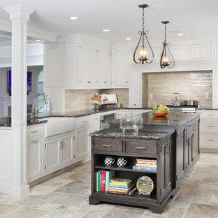 Inredning av ett klassiskt stort kök, med luckor med profilerade fronter, en rustik diskho, granitbänkskiva, travertin golv, vita skåp, beige stänkskydd, en köksö, rostfria vitvaror och stänkskydd i travertin