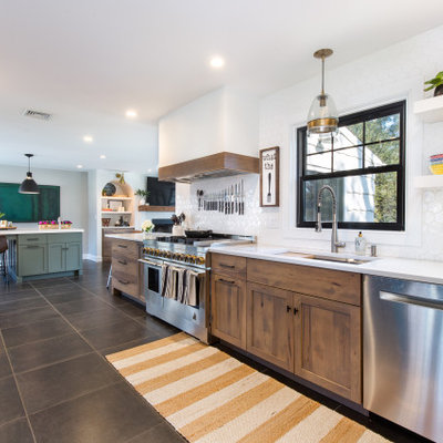 Mid-sized transitional galley ceramic tile and gray floor open concept kitchen photo in New York with an undermount sink, shaker cabinets, medium tone wood cabinets, quartz countertops, white backsplash, ceramic backsplash, stainless steel appliances, an island and white countertops