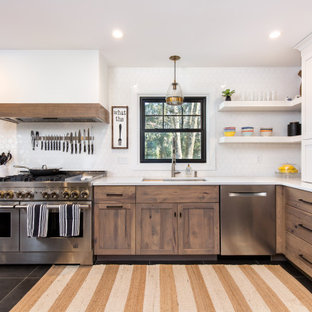 ニューヨークの中くらいのトランジショナルスタイルのおしゃれなキッチン (アンダーカウンターシンク、シェーカースタイル扉のキャビネット、中間色木目調キャビネット、クオーツストーンカウンター、白いキッチンパネル、セラミックタイルのキッチンパネル、シルバーの調理設備、セラミックタイルの床、白いキッチンカウンター、黒い床) の写真