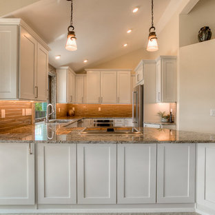 Transitional kitchen photos - Example of a transitional medium tone wood floor kitchen design in Seattle with an undermount sink, shaker cabinets, white cabinets, granite countertops, brown backsplash, stainless steel appliances and a peninsula