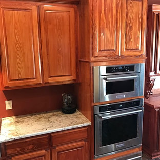 Geschlossene Klassische Küche mit profilierten Schrankfronten, braunen Schränken, Granit-Arbeitsplatte, Küchengeräten aus Edelstahl, Backsteinboden und Halbinsel in New Orleans